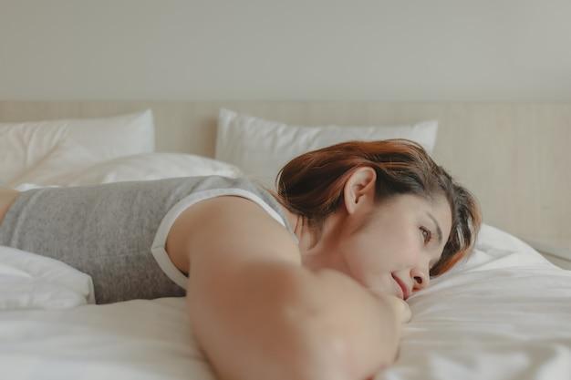 Aantrekkelijke vrouw lag op het bed en voelde zich 's ochtends ontspannen en gezellig