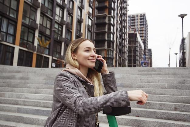 Aantrekkelijke vrouw leunt op een scooter en vertelt haar vriend over de voordelen van het huren van een elektrische auto. bellen. moderne flatgebouwen op achtergrond.