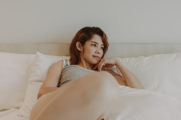 Aantrekkelijke vrouw ligt in bed op zomerochtend