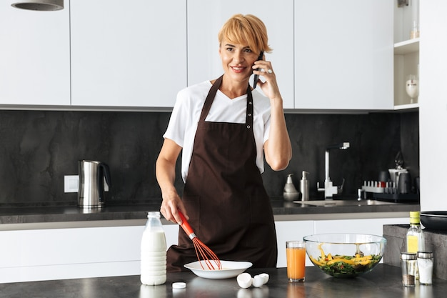 Aantrekkelijke vrouw lunch koken terwijl je in de keuken thuis, praten over de mobiele telefoon