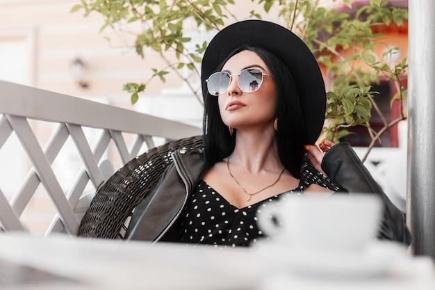 Aantrekkelijke vrouw mannequin in zwarte elegante mooie kleding in zonnebril rust zittend op vintage stoel in zomerterras op zonnige dag. sexy meisje nam koffiepauze. goedemorgen.