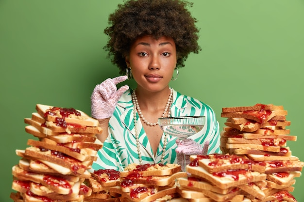 Aantrekkelijke vrouw met afro-haar, omringd door boterhammen met pindakaasgelei