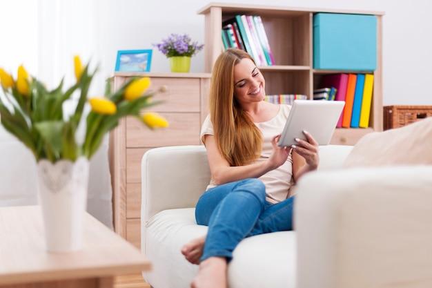 Aantrekkelijke vrouw met behulp van digitale tablet op de bank