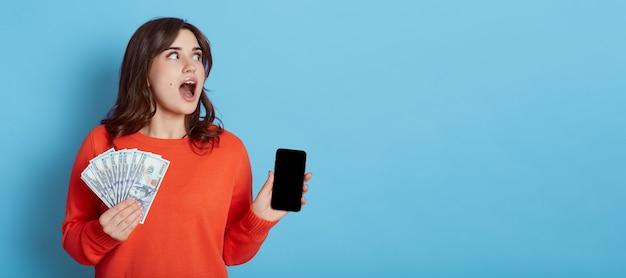 Aantrekkelijke vrouw met behulp van ongelooflijke mobiele betaaldienst, verrast vrouw met mobiele telefoon