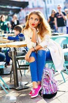 Aantrekkelijke vrouw met blond haar, sexy lachend meisje op terras, stad achtergrond. een spijkerbroek met gaten, een witte jas.