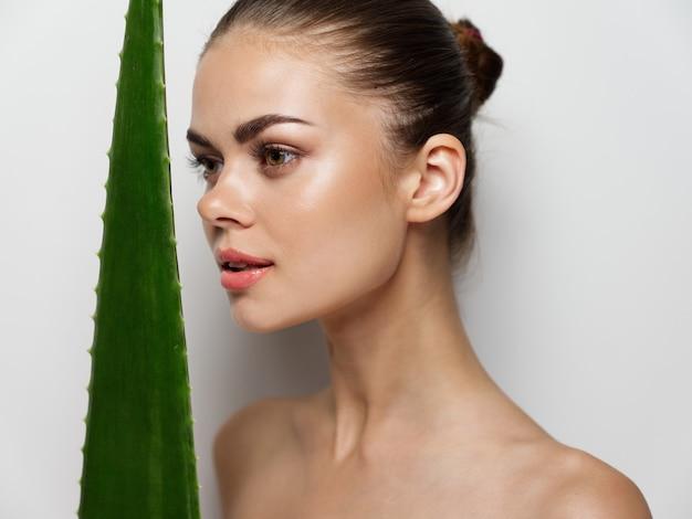 Aantrekkelijke vrouw met blote schouders en groen aloëblad schoon huid kosmetisch model