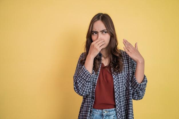 Aantrekkelijke vrouw met boze uitdrukking die de neus bedekt met de hand terwijl ze met copyspace staat