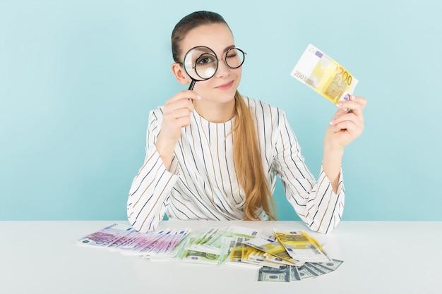 Aantrekkelijke vrouw met contant geld en vergrootglas