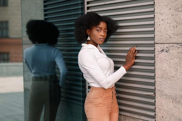 Aantrekkelijke vrouw met een donkere huid bij de muur