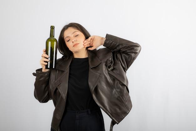 Aantrekkelijke vrouw met een fles wijn staan en poseren.