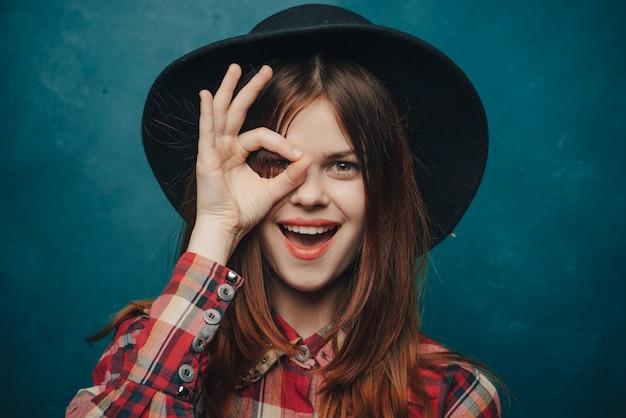 Aantrekkelijke vrouw met een hoed op haar hoofd en een plaidoverhemd met het portret van haar handen gebaren.