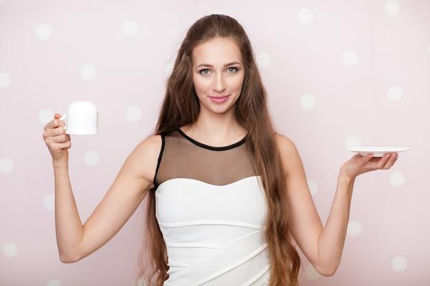 Aantrekkelijke vrouw met een lege witte kop op een roze achtergrond