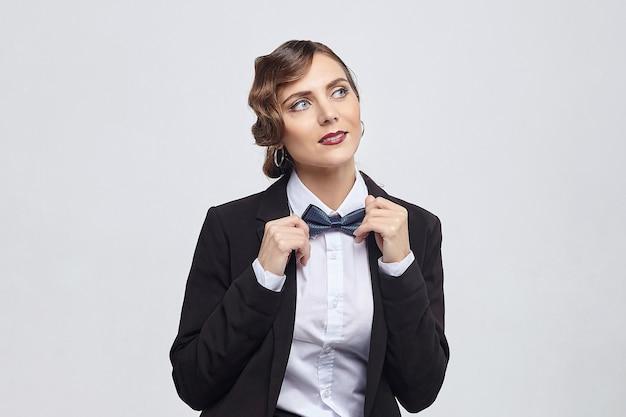 Aantrekkelijke vrouw met een retro kapsel vormt in een man's pak. fotoshoot in de studio op een witte achtergrond