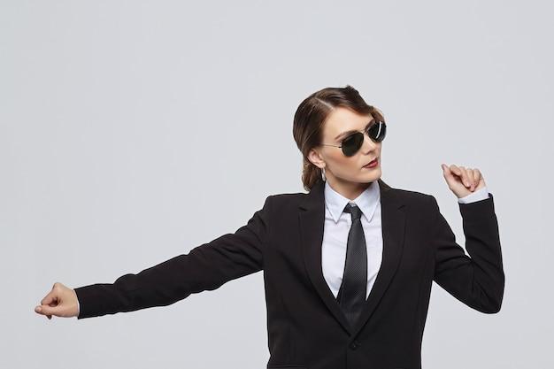 Aantrekkelijke vrouw met een retro kapsel vormt in een mannenkostuum en zonnebril