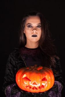 Aantrekkelijke vrouw met een serieus gezicht verkleed als een heks die een pompoen vasthoudt op een zwarte achtergrond.