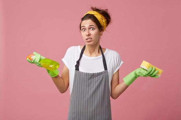 Aantrekkelijke vrouw met europees uiterlijk die schort draagt die haar schouders in verwarring ophaalt terwijl ze afwasmiddel en spons vasthoudt, niet wetend wat ze eerst moeten schoonmaken. dienstmeisje twijfelt