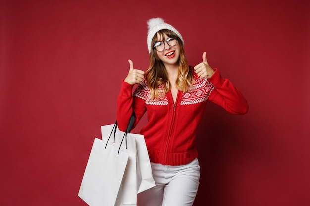 Aantrekkelijke vrouw met golvende haren staan met witte boodschappentassen