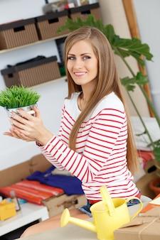 Aantrekkelijke vrouw met gras met installatiepot
