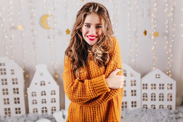 Aantrekkelijke vrouw met grijze ogen glimlacht beminnelijk, zichzelf knuffelend bij schouders. meisje in gebreide lange trui poseren tegen muur van speelgoed huizen.