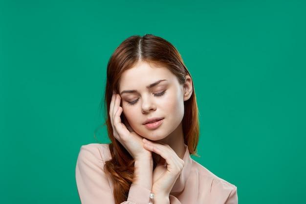 Aantrekkelijke vrouw met hand in de buurt van gezicht emotie passie model groene achtergrond. hoge kwaliteit foto