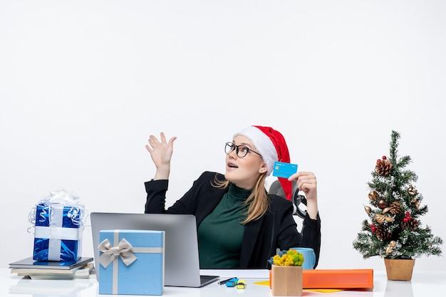 Aantrekkelijke vrouw met kerstman hoed en bril zittend aan een tafel kerstcadeau en bankkaart te houden op zoek naar boven in het kantoor