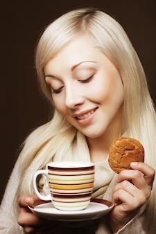 Aantrekkelijke vrouw met koffie en koekjes