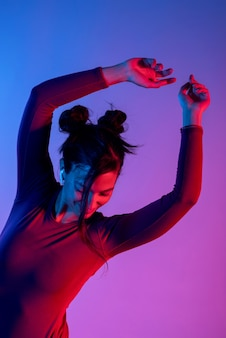 Aantrekkelijke vrouw met koptelefoon luisteren muziek in studio met blauwe en rode lichten
