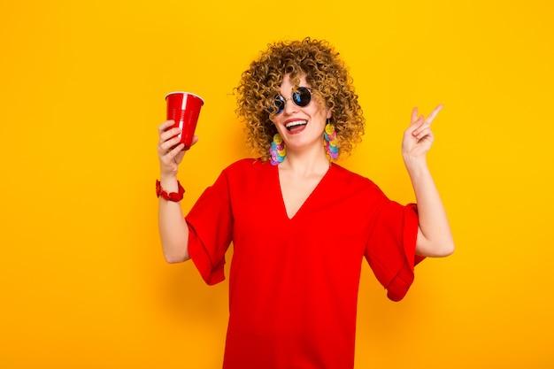 Aantrekkelijke vrouw met kort krullend haar en drankje