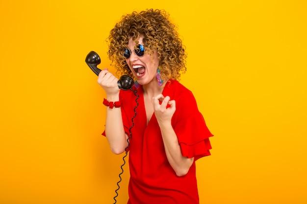 Aantrekkelijke vrouw met kort krullend haar met telefoon