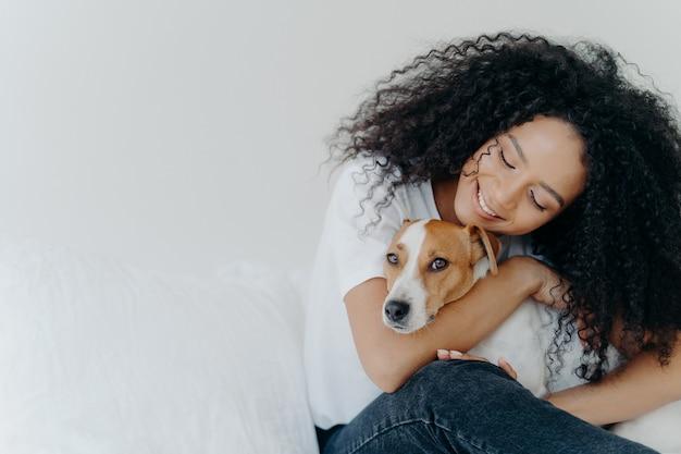 Aantrekkelijke vrouw met krullend afro-kapsel, knuffels en huisdierenhond met glimlach, spreekt liefde uit, geniet van een gezellige huiselijke sfeer