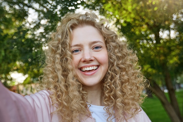 Aantrekkelijke vrouw met krullend haar en blauwe charmante ogen, aangenaam glimlachend