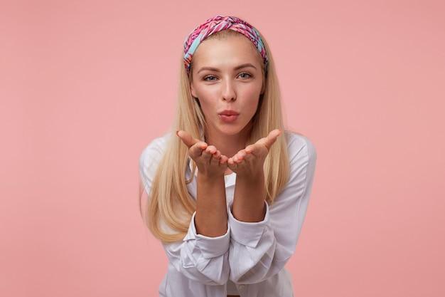 Aantrekkelijke vrouw met lang blond haar waait lucht kus en op zoek, haar goede gevoelens demonstreren, poseren