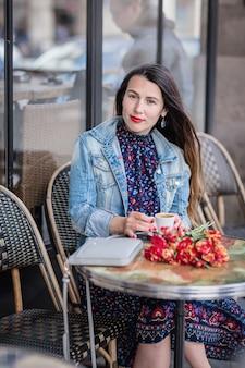 Aantrekkelijke vrouw met lang donkerbruin haar in een blauwe jurk zit alleen met bloemen in het straatcafé en koffie drinken