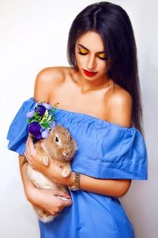 Aantrekkelijke vrouw met lang donkerbruin haar, mooie ogen, rode lippen en perfecte huid poseren in studio in blauwe jurk met konijn en bloemen