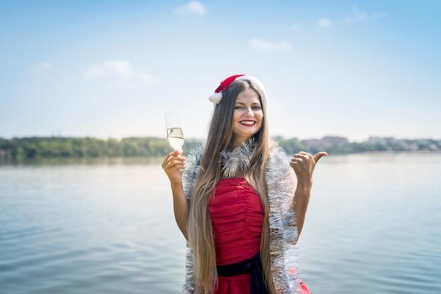 Aantrekkelijke vrouw met lang haar en champagne op strand