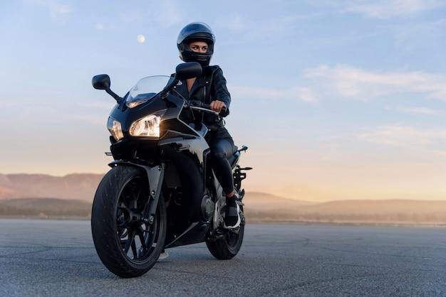 Aantrekkelijke vrouw met lang haar in zwarte leren jas en broek op buiten parkeren met stijlvolle sportmotorfiets bij zonsondergang.