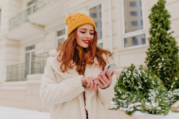 Aantrekkelijke vrouw met lang kapsel sms-bericht. winter portret van gelukkig gember meisje.