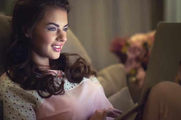 Aantrekkelijke vrouw met laptop thuis. jonge vrouw die aan computer werkt terwijl thuis het zitten op de bank. thuis genieten. low key