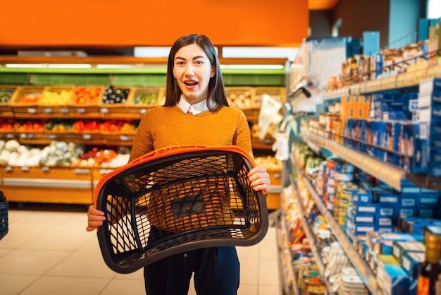 Aantrekkelijke vrouw met lege mand in supermarkt grocery