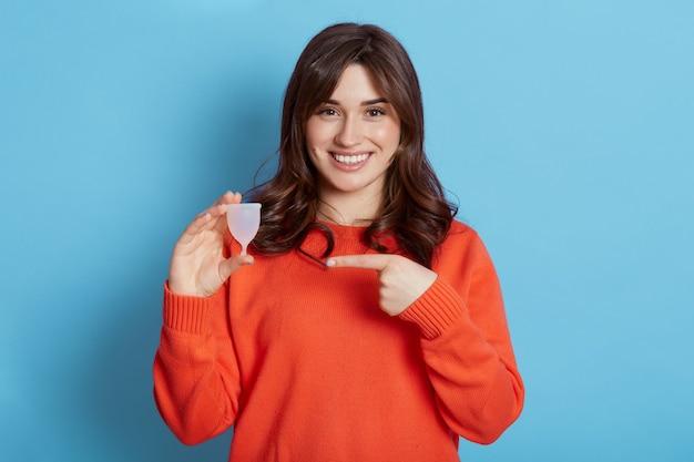 Aantrekkelijke vrouw met menstruatiecup en wijst erop met haar wijsvinger