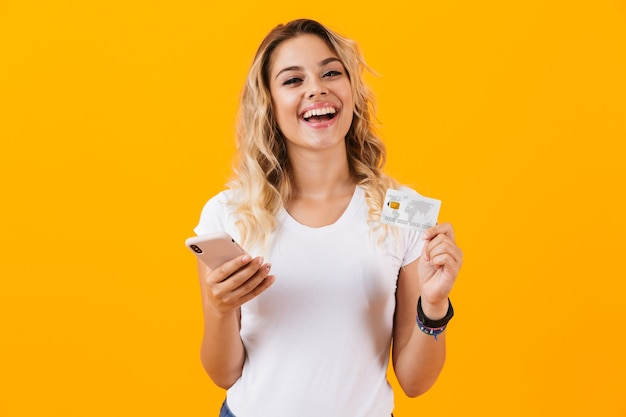 Aantrekkelijke vrouw met mobiele telefoon en creditcard in handen, geïsoleerd over gele muur