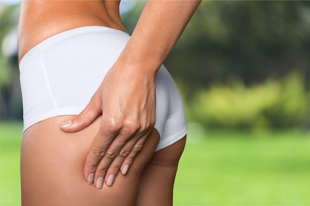 Aantrekkelijke vrouw met perfect lichaam die cellulitis op haar billen controleert, bijgesneden afbeelding