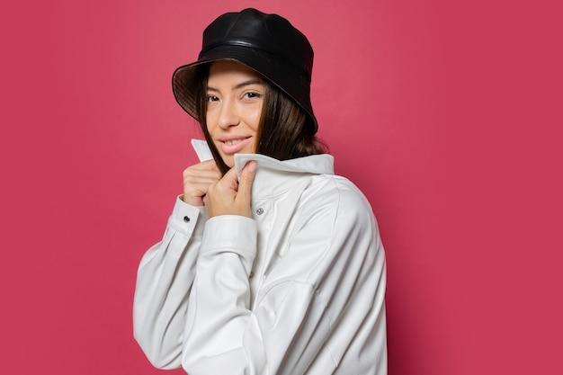Aantrekkelijke vrouw met perfecte glimlach gekleed in stijlvolle pet en witte jas poseren op roze achtergrond. isoleren.