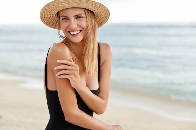 Aantrekkelijke vrouw met positieve uitdrukking, toont perfect lichaam in bikini, zonnebaadt op het strand, rust in goed gezelschap van vrienden in tropisch land, geniet van zonnig weer en zeebries