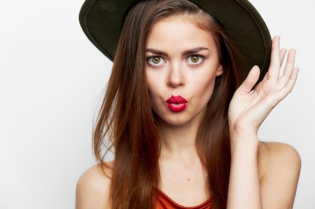 Aantrekkelijke vrouw met rode lippen die tegen de muur stellen