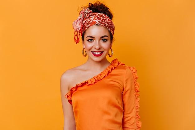 Aantrekkelijke vrouw met rode lippen in hoofddoek en zijden blouse met glimlach onderzoekt camera op oranje ruimte.