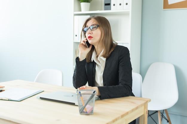 Aantrekkelijke vrouw met rode lippen in kantoor praten over de telefoon