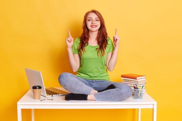 Aantrekkelijke vrouw met rood haar en het charmante glimlach stellen op bureau dichtbij laptop