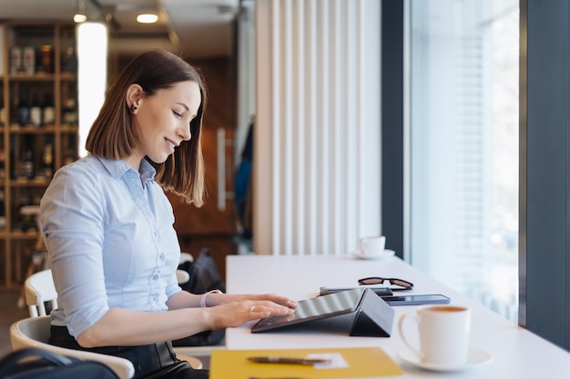 Aantrekkelijke vrouw met schattige glimlach met een kopje koffie terwijl relaxin in een pauze met een digitale tablet