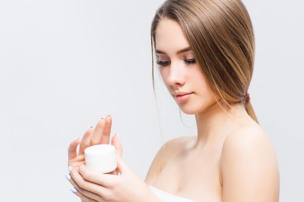 Aantrekkelijke vrouw met schoonheidscrème op haar hand